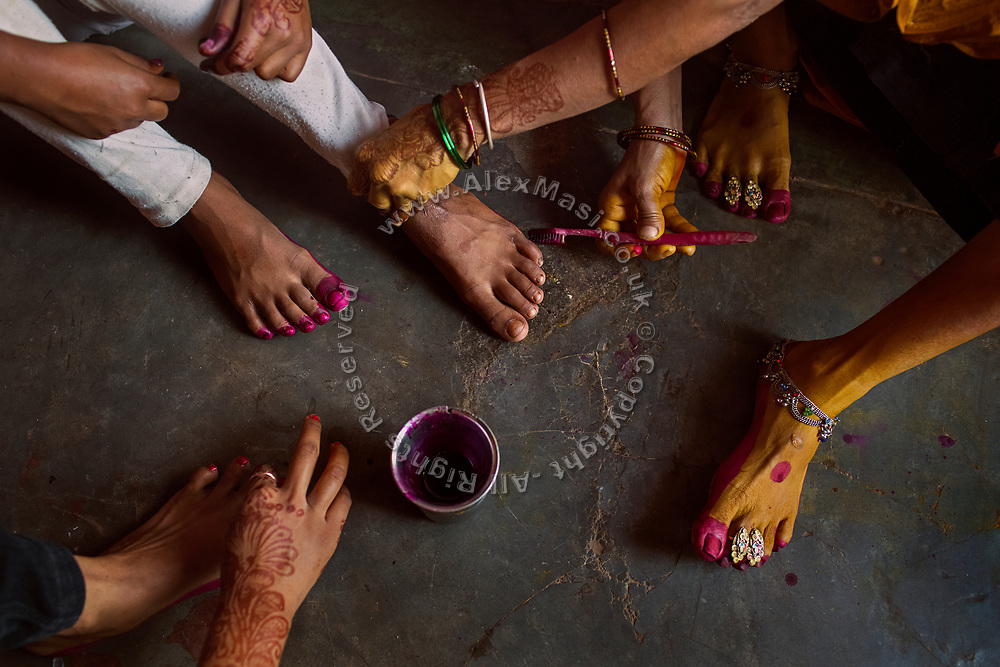 Using a toothbrush, Poonam, 14, her sister Jyoti, 15, and their mother Sanjita, 43, are decorating their feet with colours while sitting on the floor of their newly built home in Oriya Basti, one of the water-contaminated colonies in Bhopal, central India, near the abandoned Union Carbide (now DOW Chemical) industrial complex, site of the infamous '1984 Gas Disaster'.