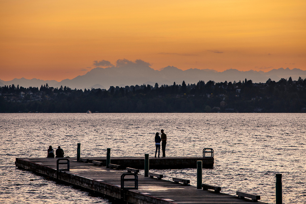 United States, Washington, Kirkland, couple on dock on Lake Washington at sunset.