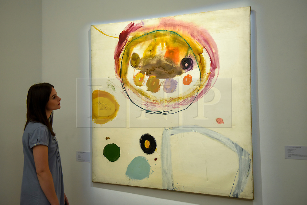 """© Licensed to London News Pictures. 17/07/2019. LONDON, UK. A staff member views """"Snare"""", 1962, by Gillian Ayres at the preview of """"Brave New Visions: The Émigrés who transformed the British Art World"""", a new exhibition at Sotheby's gallery in New Bond Street which runs 17 July to 9 August 2019.  The show is also part of """"Insiders / Outsiders"""", a nationwide, year long festival celebrating refugees from Nazi Europe and their contribution to British culture.  Photo credit: Stephen Chung/LNP"""