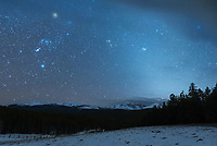 The constellation Orion hangs above the snowy peaks of the Bighorn Mountains on a cold and windy night. The diffuse glow on the right is called the zodiacal light. This glow can only be seen where the skies are very dark, any light pollution will drown it out. The zodiacal light is caused by the sun reflecting off of grains of dust shed by comets and asteroids in the inner solar system. This dust is concentrated along the zodiac (also known as ecliptic), which is the orbital plane that the sun, moon, and planets travel in our sky. The planet Mars can be seen touching a cloud at the bottom of the glow. Because of the angle of the ecliptic, this phenomena is best seen in the west after dusk in the spring, or in the east before dawn in the fall.