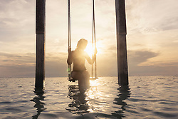 Woman sitting on rope swing at beach against sunset, Gili Trawangan, Lombok, Indonesia