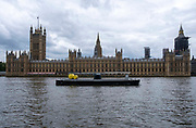 A barge sits moored up in the river Thames outside the The Palace of Westminster, also known as the Houses of Parliament  or the House of Commons on the 25th of May 2021.  It is the meeting place of the governments of the United Kingdom and is on the bank of the river Thames in London.