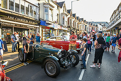 © Licensed to London News Pictures. 27/08/2021. Swansea, UK. People stop to view  a replica of a Bugatti Type 35 in the village of Mumbles, Swansea, as it is taken over by vintage cars. The event saw the main street closed to traffic and full of historic vehicles and replicas, ranging from E-Type Jaguars, to modern day classics Photo credit: Robert Melen/LNP