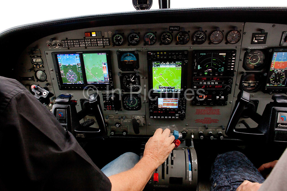 Pilot in the cockpit of a small airplane. Amazon edge, a Cessna Caravan light aircraft is ownbed by Greenpeace and used to monitor and investigate deforestation from logging and the Belo Monte Hydroelectric dam. Altamira, Para, Brazil.