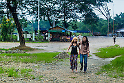 14 JUNE 2013 -  SAMALAUK, AYEYARWADY, MYANMAR:  Burmese friends, one with her hair dyed blonde, walk through the rain along Highway 5 in Samalauk, Ayeyarwady, in the Irrawaddy delta region of Myanmar. Most Burmese men join the clergy at least once in the lives, sometimes for just a few weeks, other times for a lifetime commitment. This region of Myanmar was devastated by cyclone Nargis in 2008 but daily life has resumed and it is now a leading rice producing region.  PHOTO BY JACK KURTZ