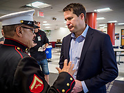 25 APRIL 2019 - DES MOINES, IOWA: US Representative SETH MOULTON (D-MA), left, talks to MANUEL VALENZUELA, a US Marine veteran of the Vietnam War, in the lobby of Central Academy. Rep. Moulton visited Central Academyl in Des Moines Thursday to talk to high school students and the school's JROTC class about public service. Moulton, a US Marine veteran who served in Iraq, is running to be the Democratic candidate for the US Presidency in 2020. Iowa traditionally hosts the the first selection event of the presidential election cycle. The Iowa Caucuses will be on Feb. 3, 2020.      PHOTO BY JACK KURTZ