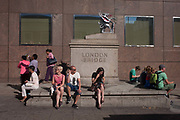 Londoners and visitors sit beneath the Griffin marking the southern boundary of the City of London, on the southern side of London Bridge, on 15th August 2016 in the City of London, UK. This scene is on the borough of Southwark side but the bridge to the left in this picture is still technically part of the governing Corporation of London who administer the modern district founded by the Romans in the 1st century. Today, the Citys outer boundaries are marked by the Griffins.