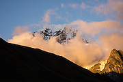 """Sunrise hits the East Face of Siula Grande (20,814 ft or 6344 m) in the Cordillera Huayhuash, Andes Mountains, Peru, South America. Day 3 of 9 days trekking around the Cordillera Huayhuash. Siula Grande was the subject of the gripping 2003 British docudrama """"Touching the Void."""" In 1985, climbers Joe Simpson and Simon Yates scaled the treacherous West Face of Siula Grande, but after Joe broke his leg, their descent became one of the most amazing survival stories in mountaineering history. The 2003 movie is based upon Joe Simpson's harrowing book, """"Touching the Void: The True Story of One Man's Miraculous Survival."""""""