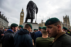 © Licensed to London News Pictures. 28/10/2015. London, UK. Former and serving members of the armed forces stand underneath a statue of Winston Churchill as they take part in a rally in support of support of Sgt Alexander Blackman, who was given a life sentence after being convicted of murdering a wounded Taliban fighter. Senior military officials have warned of possible disciplinary action against troops caught attending the event. Photo credit: Ben Cawthra/LNP