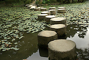 Stepping stones over a water lily pond in a zen garden at the Heian Shrine in Kyoto Japan