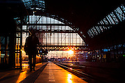 Een reiziger loopt over een perron op het centraal station van Amsterdam in avondlicht.<br /> <br /> A traveler is walking at a platform at Amsterdam Central Station at dusk.