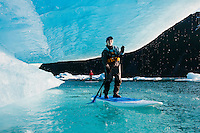 Two women on stand up paddle boards (SUP) paddle under a wave of ice as it drips on Bear Lake in Kenai Fjords National Park, Alaska.
