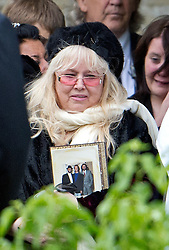© London News Pictures. 08/06/2012. Thame, UK.   Dwina Gibb, wife of Robin Gibb carrying a photograph of all three Bee Gee's as she leaves  St Mary's Church in Thame, Oxfordshire following the funeral of Robin Gibb on June 8, 2012. Robin Gibb died on May 20, 2012 aged 62 following a long battle against cancer. Photo credit: Ben Cawthra/LNP