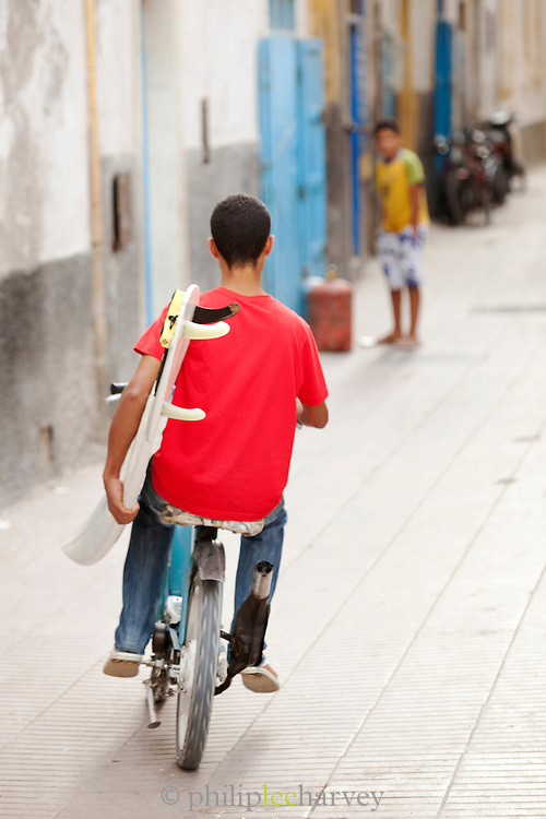 A boy cycles through the medina carrying a surf board in Essaouira, Morocco