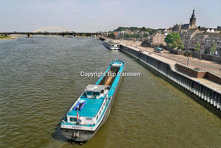 Nederland, Nijmegen, 25-7-2019 Een leeg binnenvaartschip vaart over de Waal bij Nijmegen.Het schip gaat aanleggen aan de kade . Foto: ANP/ Hollandse Hoogte/ Flip Franssen