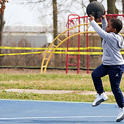 Toledo resident Houston Kincaid, 6, plays with his basketball while with his dad at the Jamie Farr Park basketball court in Toledo on Thursday, March 26, 2020. Caution tape is seen on the playground equipment in the background due to playground closures amid the COVID-19 outbreak. THE BLADE/KURT STEISS