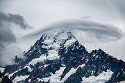 Seen from the Sealy Tarns Track, a stationary lenticular cloud caps the peak of Aoraki / Mount Cook (3755 meters / 12,349 feet) in Aoraki / Mount Cook National Park, Southern Alps, Canterbury region, South Island, New Zealand. In 1990, UNESCO honored Te Wahipounamu - South West New Zealand as a World Heritage Area.