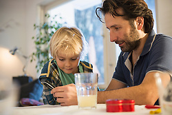 Father with son using smart phone at home