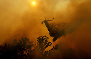 A helicopter drops water on flames a fire in Fallbrook, California May 14, 2014.  Television news footage has shown several homes burning as high temperatures and winds drove the flames into neighborhoods, burning 100 acres thus far. REUTERS/Sandy Huffaker   (UNITED STATES)