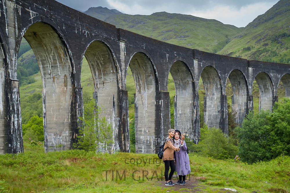 Tourists posing for selfies at famous Glenfinnan Viaduct tourist spot in the Highlands of Scotland