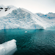 A low-lying iceberg protrudes much further under the water in Curtis Bay, Antarctica, making the water appear green.