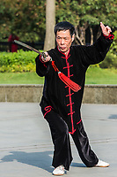 Shanghai, China - April 7, 2013: one man exercising tai chi with traditional costume in gucheng park in the city of Shanghai in China on april 7th, 2013