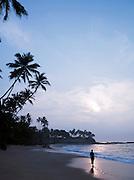 Man walking along a sandy beach at dawn in Tangalle, Sri Lanka