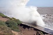 High energy waves eroding sea-wall, Bawdsey, Suffolk, England