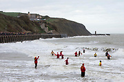 Closely watched by life guards locals enter the sea for the Folkestone Lions Club Boxing Day Dip.  An annual fancy dress fundraising event, where all sorts of amusing costumes and characters enter the cold sea of the English Channel at Sunny Sands, Folkestone. UK.