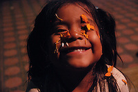 """MEXICO, Veracruz, Tantoyuca, Oct 27- Nov 4, 2009. A young girl plays under a shower of orange """"cempasuchil"""" flowers in Tantoyuca's """"Plaza Constitucion.""""""""Xantolo,"""" the Nahuatl word for """"Santos,"""" or holy, marks a week-long period during which the whole Huasteca region of northern Veracruz state prepares for """"Dia de los Muertos,"""" the Day of the Dead. For children on the nights of October 31st and adults on November 1st, there is costumed dancing in the streets, and a carnival atmosphere, while Mexican families also honor the yearly return of the souls of their relatives at home and in the graveyards, with flower-bedecked altars and the foods their loved ones preferred in life. Photographs for HOY by Jay Dunn."""