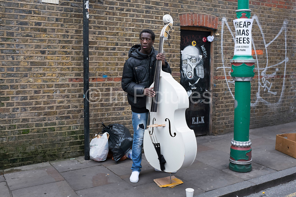 Street scene with a young busker playing a white double bass, whilst rapping at Brick Lane Market in the East End of London, UK. This area is known for it's eclectic, brilliant, sometimes bizarre fashion as young people meet up on Sunday, market day, and time for people to gather, hang out, and maybe find a bargain.