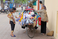 Woman Buying Clothes From Bicycle Vendor