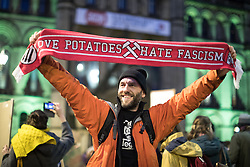 © Licensed to London News Pictures . 20/02/2017 . Manchester , UK . Man with a LOVE POTATOES HATE FASCISM scarf . Hundreds of protesters at a Stop Trump demonstration in Albert Square , central Manchester , to coincide with Parliament debating a petition calling for the government to cancel a State Visit by US President Donald Trump . Photo credit: Joel Goodman/LNP