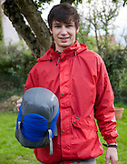 Model released teenager boy wearing red waterproof jacket and holding a sleeping bag, UK