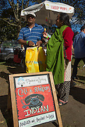 A man and a woman sample Monsieur Singh's lassi pops. The sign invites anyone to call a random Indian to ask why they love lassi.
