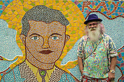 American artist Anado McLauchlin stands by a tile mosaic of his father Jimmy Ray Mclaughlin in his art compound Casa las Ranas September 28, 2017 in La Cieneguita, Mexico.