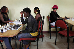 Phiona Mutesi, center left, a 14-year-old chess prodigy, plays chess in Kampala, Uganda, Dec. 11, 2010. Mutesi lives in the slums of Uganda and is just now learning to read. But her instincts have made her a player to watch in international chess. Mutesi, a naturally talented chess player is coached by Robert Katende of Sports Outreach Ministry. The chess club meets at the Agape Church inside Katwe, the largest slum in Kampala.