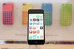 © Licensed to London News Pictures. 27/10/2013. London, UK. An Apple iPhone 5C on display at Apple's UK flagship store in Regent Street, today 27 October.  Apple is to announce its Q4 Fiscal Results tomorrow - the company launched the iPhone 5C in the closing weeks of  the quarter to as a lower cost option in an effort to attract budget users.  . Photo credit : Richard Isaac/LNP