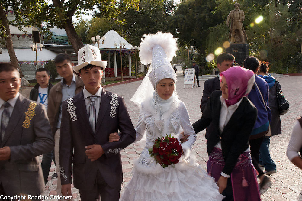 Newlyweds in traditional Kyrgyz costumes stroll with their families and pose for photographs in the park at the base of Sulaiman Too (Solomon's mountain), in Osh (Kyrgyzstan).