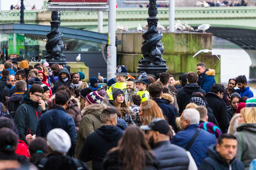 London, December 31 2017. Police in high visibility jackets and numerous anti-terrorism and crowd control measures are in place in the capital ahead of the New Year's Eve fireworks and revelry in central London. PICTURED: Police officers on the South Bank pose for pictures with a tourist. © SWNS