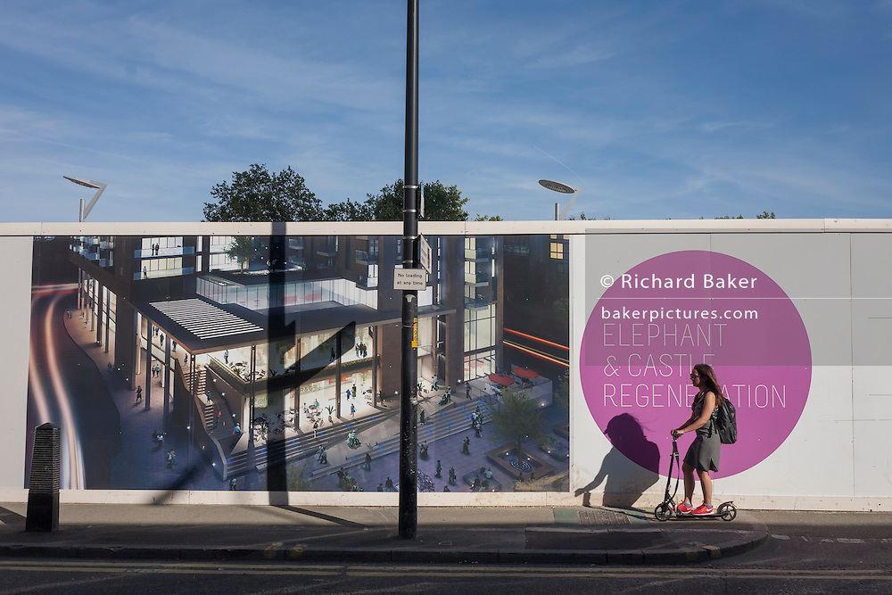 A local scoots past a construction hoarding showing the future regenerated development at Elephant & Castle, south London.