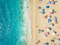 NIKITAS, GREECE - 13 JULY 2018: Aerial view of people under colourful parasols and bathers in turquoise sea.
