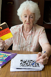 Woman using a German dictionary and doing a crossword,