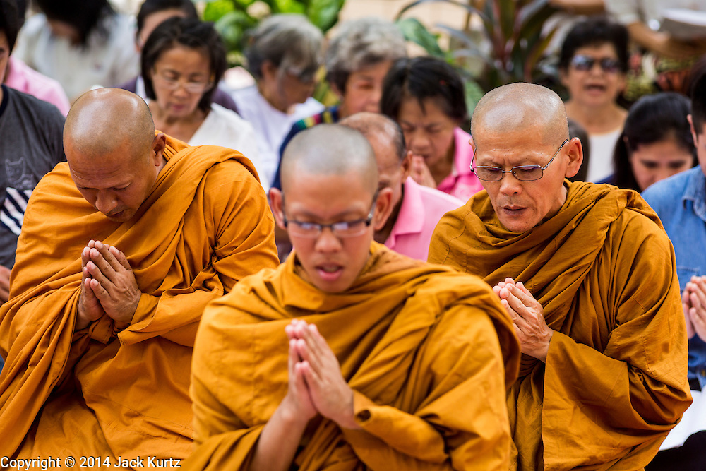 09 OCTOBER 2014 - BANGKOK, THAILAND: Buddhist monks lead a prayer service for Bhumibol Adulyadej, the King of Thailand in the plaza in front of Siriraj Hospital. The King has been hospitalized at Siriraj Hospital since Oct. 4 and underwent emergency gall bladder removal surgery Oct. 5. The King is also known as Rama IX, because he is the ninth monarch of the Chakri Dynasty. He has reigned since June 9, 1946 and is the world's longest-serving current head of state and the longest-reigning monarch in Thai history, serving for more than 68 years. He is revered by the Thai people and anytime he goes into the hospital thousands of people come to the hospital to sign get well cards.   PHOTO BY JACK KURTZ