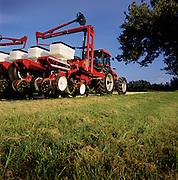 A modern seeder and tractor moves between farm fields.