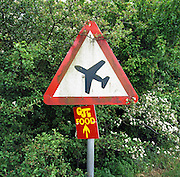 "Near the end of the military runway at RAF Mildenhall in Suffolk England, a road sign warns of low-flying aircraft near the base which is populated by the United States Air Force Refuelling Wing. Beneath the triangular sign is a locally made makeshift advertisement for CJ's, a nearby cafe. It is summer and the shrubs are green with white flowers to the side. The sign itself has become discoloured with green algae after being rained on over successive wet weather days. In the UK, the Highway Code for road-users lists this warning sign (always triangular) as ""Low-flying aircraft or sudden aircraft noise."" Picture from the 'Plane Pictures' project, a celebration of aviation aesthetics and flying culture, 100 years after the Wright brothers first 12 seconds/120 feet powered flight at Kitty Hawk,1903. ."