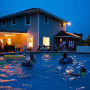 Summertime swim party at a southern home as night falls.