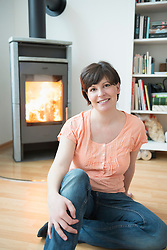 Portrait of woman sitting in his living room with fireplace, smiling