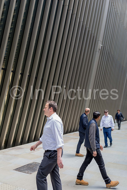 Beneath new architecture, City workers and businessmen walk along Bevis Marks in the City of London, the capitals financial district, on 17th June 2019, in London, England.