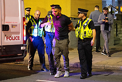 © Licensed to London News Pictures . 18/06/2021. Manchester, UK. Police cuff and detain a man before leading him in to a cell in a police van , on Peter Street , following the European Cup tie between England and Scotland at Wembley Stadium . Photo credit: Joel Goodman/LNP